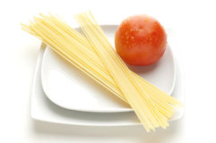 Dish with raw spaghetti. And tomato Royalty Free Stock Image