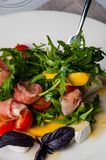 Dish in the restaurant fresh salad with basil, prosciutto, tomato and mozzarella.  royalty free stock images