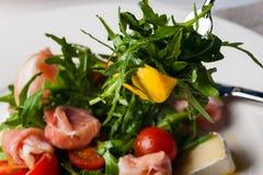 Dish in the restaurant fresh salad with basil, prosciutto, tomato and mozzarella.  royalty free stock photo