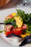Dish in the restaurant fresh salad with basil, prosciutto, tomato and mozzarella.  stock photo
