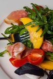 Dish in the restaurant fresh salad with basil, prosciutto, tomato and mozzarella.  royalty free stock image