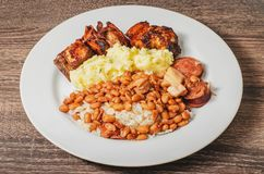 Dish with rice and beans arroz com feijao seasoned with sausag. Brazilian cuisine, dish with rice and beans arroz com feijao seasoned with sausage and bacon Royalty Free Stock Photos