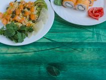 Dish with rice and salmon sushi on a white plate on a green wooden background top side view. Poke healthy food royalty free stock images