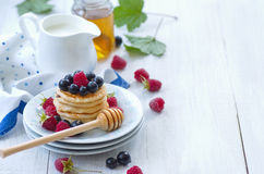 Dish with ripe raspberries, black currants and pancakes Stock Photos