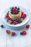 Dish with ripe raspberries, black currants and pancakes Stock Photo