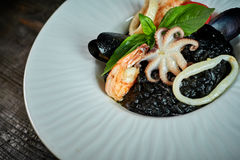 Dish of risotto with squid ink on grey plate jpg Royalty Free Stock Image