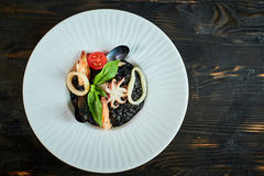 Dish of risotto with squid ink on grey plate jpg Stock Photos