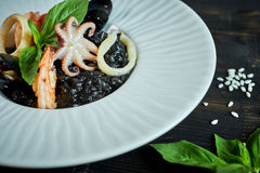Dish of risotto with squid ink on grey plate jpg Royalty Free Stock Photos