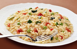 Dish of risotto zucchini peas tomatoes with fork Stock Photo