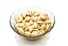 Dish with roasted pistachios. On white background Stock Photos