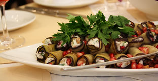Dish with rolls from eggplants. Stuffed vegetables and a pomegranate with parsley Stock Image