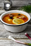 Dish of Russian cuisine-beef stew. Traditional solyanka with smoked meat products in the iron bowl Stock Photo