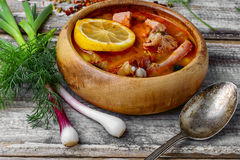 Dish of Russian cuisine-beef stew. Traditional Solyanka with smoked meats in wooden plate Royalty Free Stock Photos