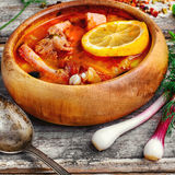 Dish of Russian cuisine-beef stew. Traditional Solyanka with smoked meats in wooden plate Royalty Free Stock Photo