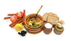 Dish of russian hodgepodge soup in ceramic pot and other foodstu Royalty Free Stock Photo