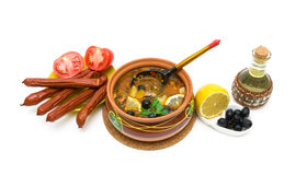 Dish of russian hodgepodge soup in ceramic pot on a white backgr Stock Photos