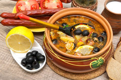 Dish of russian hodgepodge soup and other food on a wooden table Stock Photo