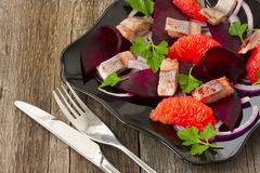 Dish with a salad of herring, beetroot and grapefruit Royalty Free Stock Images