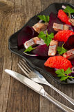 Dish with a salad of herring, beetroot and grapefruit Stock Photo
