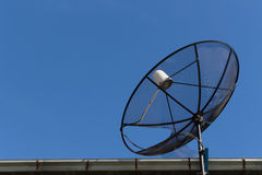 Dish satellite receiver on roof with blue sky Royalty Free Stock Photo