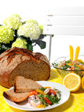 Dish with schrimp salad. TAble with yellow cloth, plate with bread and shrimp salad. In the background flower, lemons and salad bowl Stock Photo