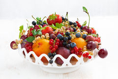 Dish with seasonal fruit and berries on white table Royalty Free Stock Images