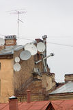 Dish-shaped aerials. On the old roof Stock Images