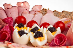 Dish with sliced ham, bacon, salami. Sliced ham, bacon, salami rolls, boiled eggs with black caviar and more Stock Photography