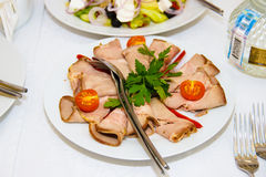 Dish of sliced pork. Cold appetizer on the table. The food for the Banquet. Holiday. A plate with pieces of meat. Serving. The table decorations, the Stock Images