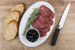 Dish with smoked sausage, black olives, twig of rosemary, bread Stock Photo