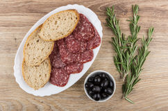 Dish with smoked sausage, bread, twigs of rosemary and olives Royalty Free Stock Photo