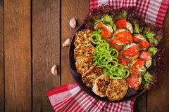 Dish with a snack of fried zucchini with tomatoes and succulent chicken cutlets with zucchini. Royalty Free Stock Image