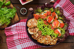 Dish with a snack of fried zucchini with tomatoes and succulent chicken cutlets with zucchini. Royalty Free Stock Photo