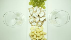 A dish with a snack is put on the table, two glasses for wine and poured. Top view. A dish with cheese, grapes and crackers is put on the table, two glasses for stock footage