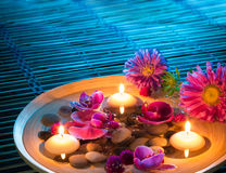 Dish spa with floating candles, daisys, orchid on mat. Composition with candles for bath stock image
