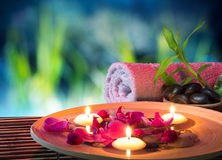 Dish spa with floating candles, orchid. Bambu towel in garden stock images