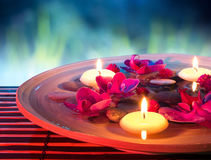 Dish spa with floating candles, orchid, in garden. Composition with candles for bath royalty free stock photo