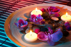 Dish spa with floating candles, orchid on mat. Composition with candles for bath royalty free stock photo
