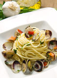 Dish of spaghetti with clams. On wooden table Royalty Free Stock Images