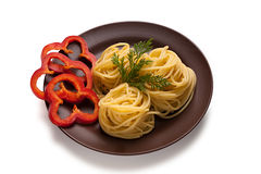 Dish with spaghetti and pepper. Cooked spaghetti with peppers on a clay plate Royalty Free Stock Photo