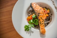 Dish of stir fired spaghetti with grilled salmon on top. On wooden table Stock Images