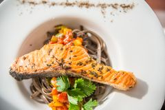 Dish of stir fried spaghetti with grilled salmon on top. On wooden table in restaurant Stock Photo