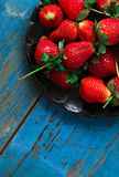 A dish of strawberries. A plate of strawberries on a blue table Royalty Free Stock Images