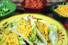 A dish of tacos and bowls of toppings. A colorful plate of tacos and toppings Royalty Free Stock Photography