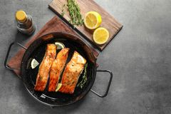 Dish with tasty cooked salmon on table. Top view Royalty Free Stock Photo
