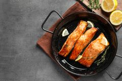 Dish with tasty cooked salmon on table. Top view Royalty Free Stock Image