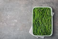 Dish with tasty green beans on table. Top view royalty free stock images