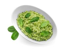 Dish with tasty spinach risotto. On white background stock photo