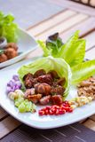 A dish of Thai style fermented sausage with side herbs, chili, lime, ginger, cashew nut. garlic and shallot on dining table. A dish of Thai style fermented stock images