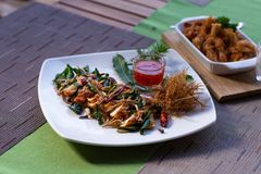 A dish of Thai style fried chicken with side herbs, lemongrass and kaffir lime leaves with sweet sauce on dining table. A dish of Thai style fried chicken with royalty free stock photography